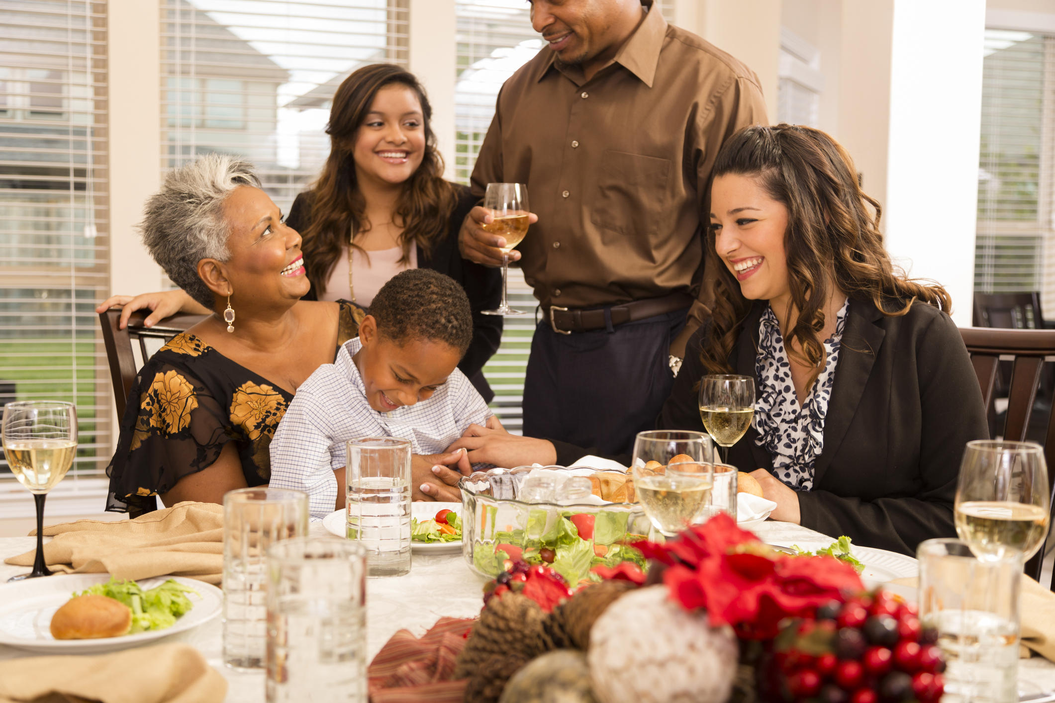 Multi-ethnic group of family and friends gather together at grandmother's home for Christmas dinner or a holiday party. Food dishes and wine on the dining room table. African and Latin descent family members.  Aunt tickles little boy, who is sitting in grandmother's lap.
