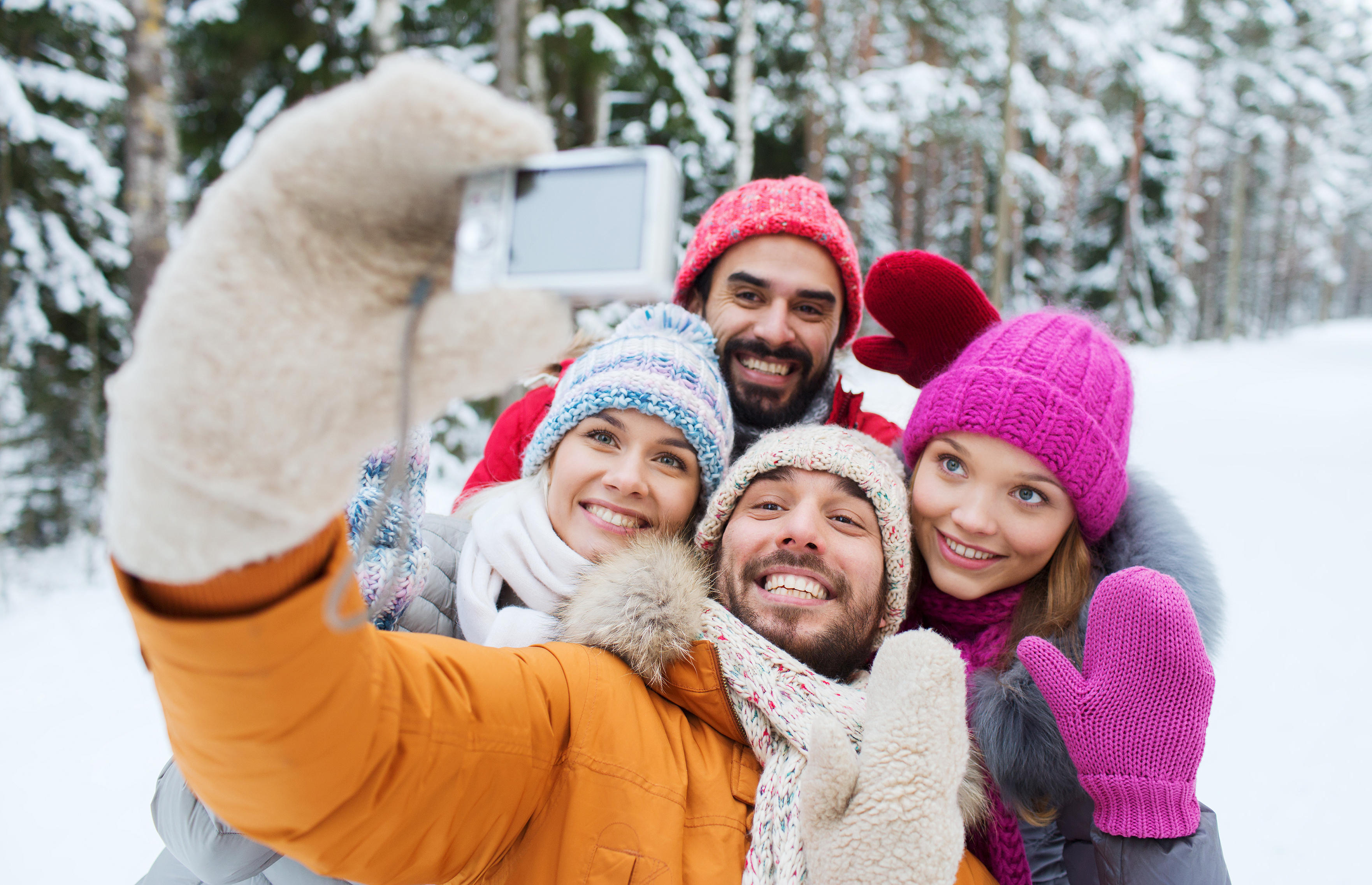 technology, season, friendship and people concept - group of smiling men and women taking selfie with digital camera in winter forest