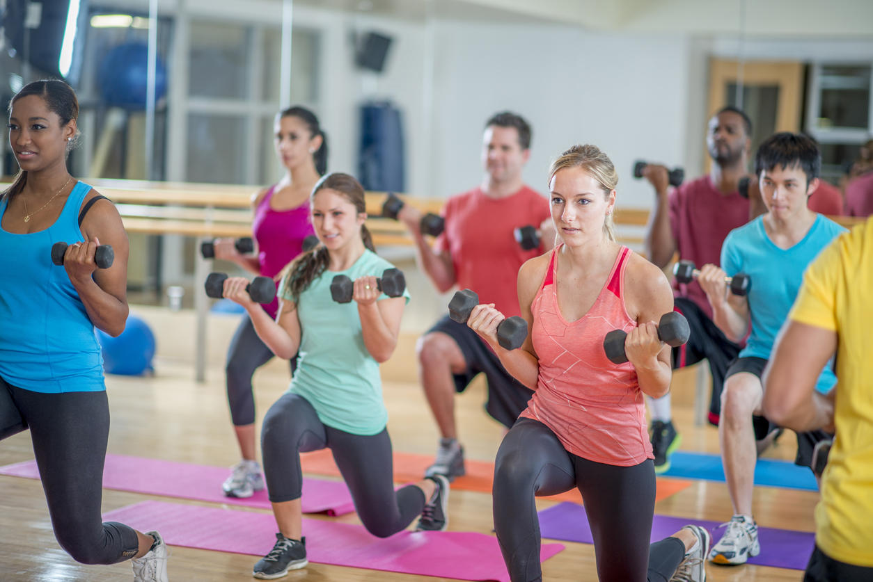A multi-ethnic group of young adults are working out together in a aerobic fitness class at the gym. They are doing forward lunges with weights on their fitness mats.