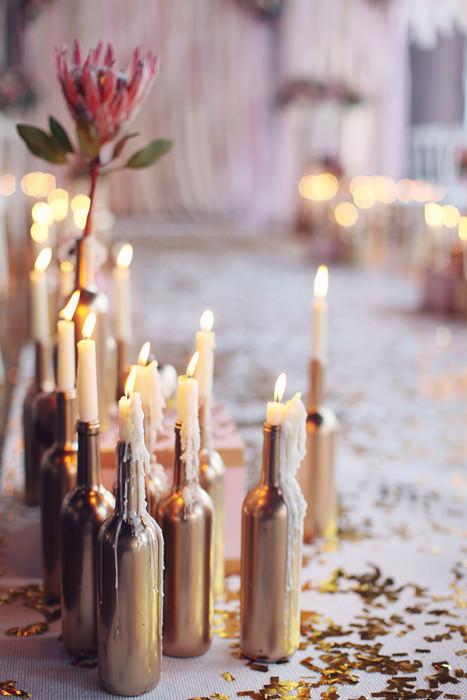 Candles in metallic wine bottles