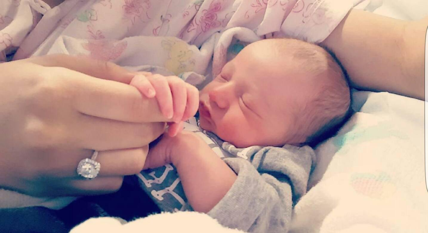 newborn with engagement ring