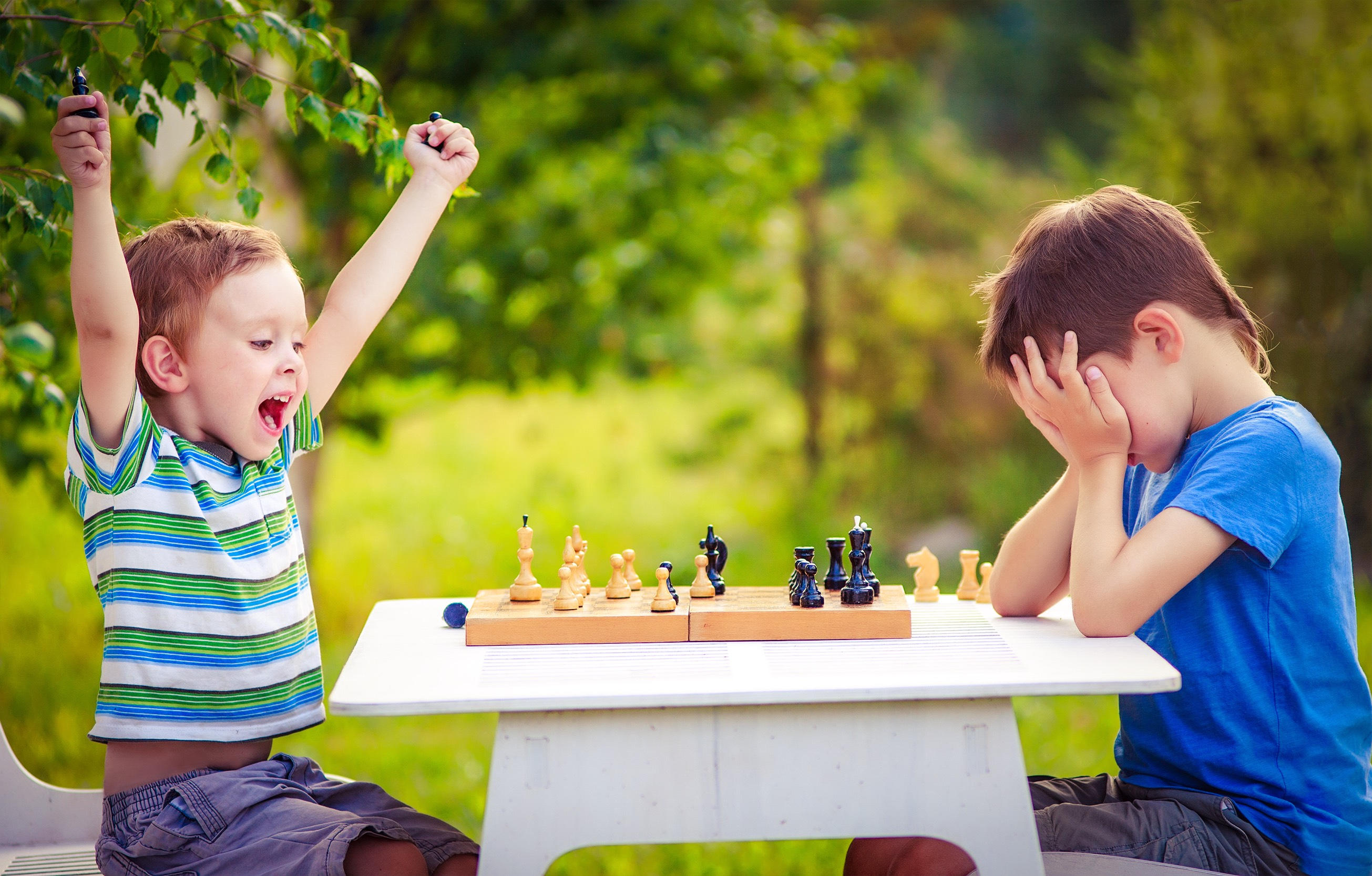 two young chess players outdoors. boy rejoices won a game of chess. sad opponent covered his face, and upset losing