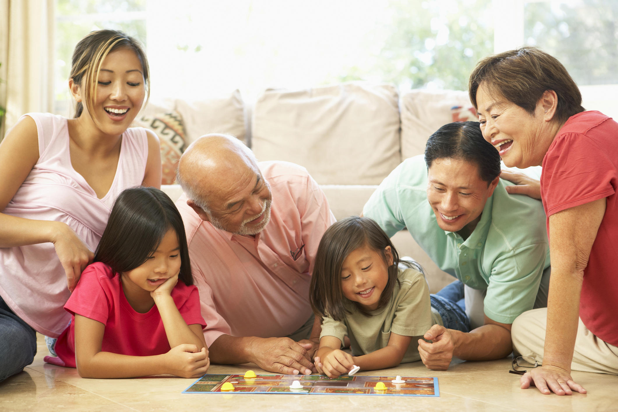 Extended Family Group Playing Board Game In Living Room At Home