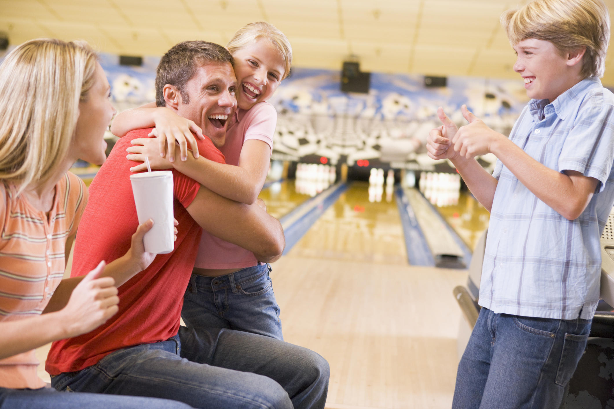 Family in bowling alley cheering and smiling. Family celebrating together, Father and daughter embracing.