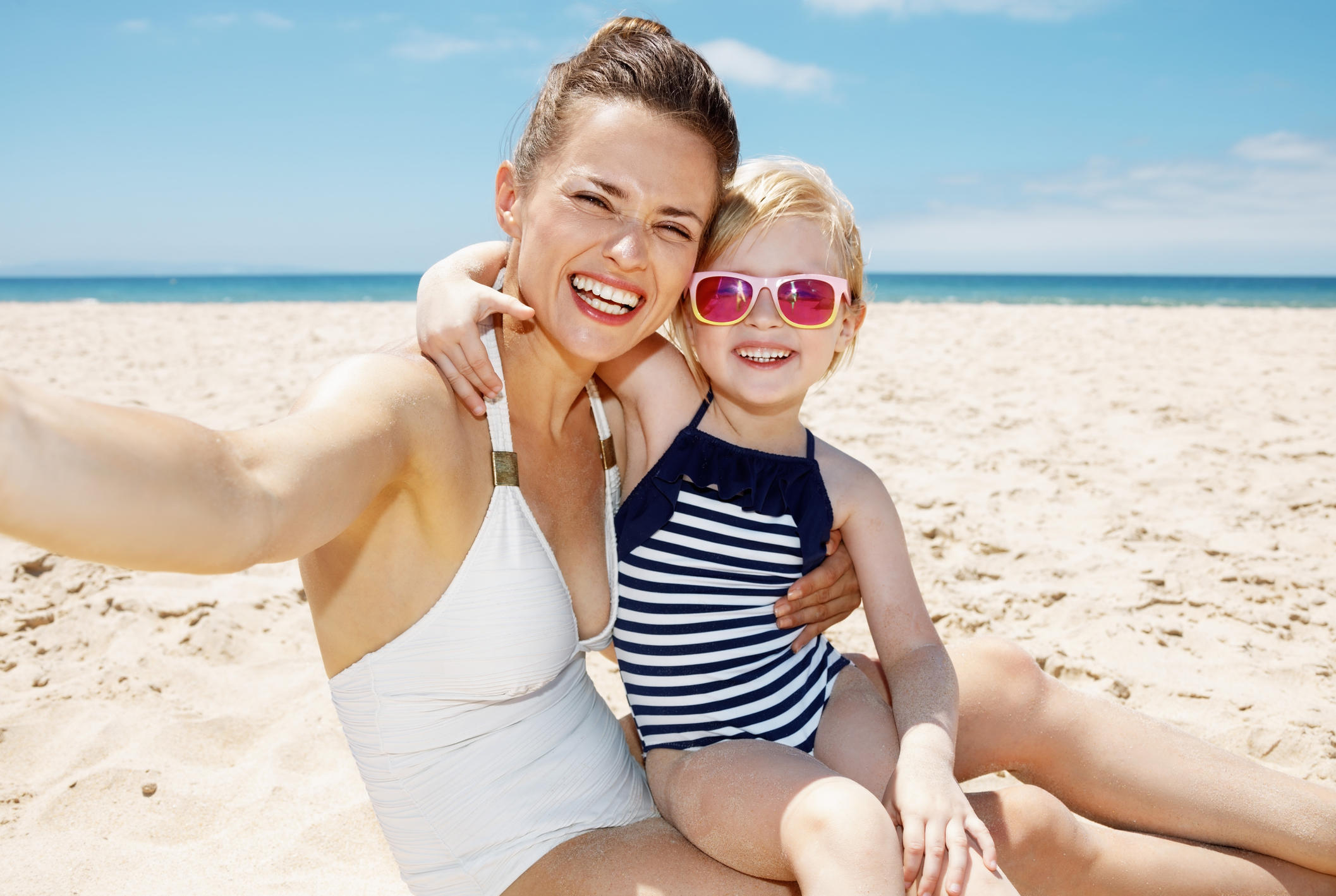 Smiling mom and kid at the beach