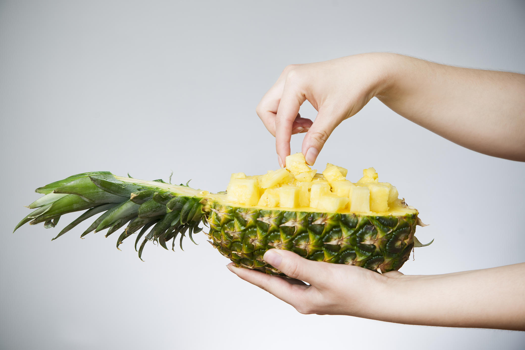 Pineapple in female hands on gray background. Weight loss, diet