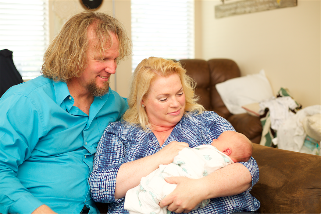 Janelle and Kody Brown hold grandson Axel Brush