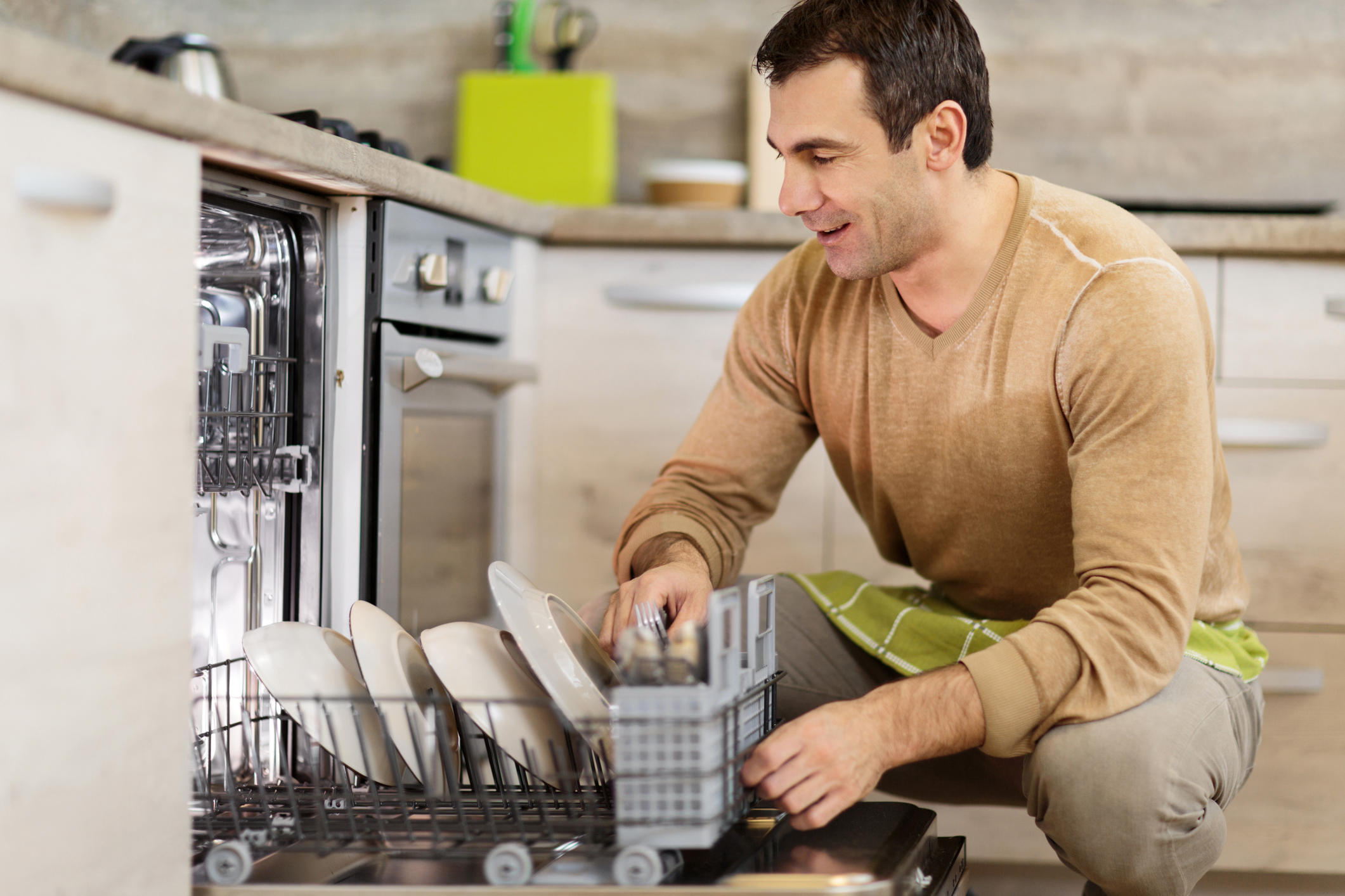 Mid adult man using dishwasher in the kitchen.