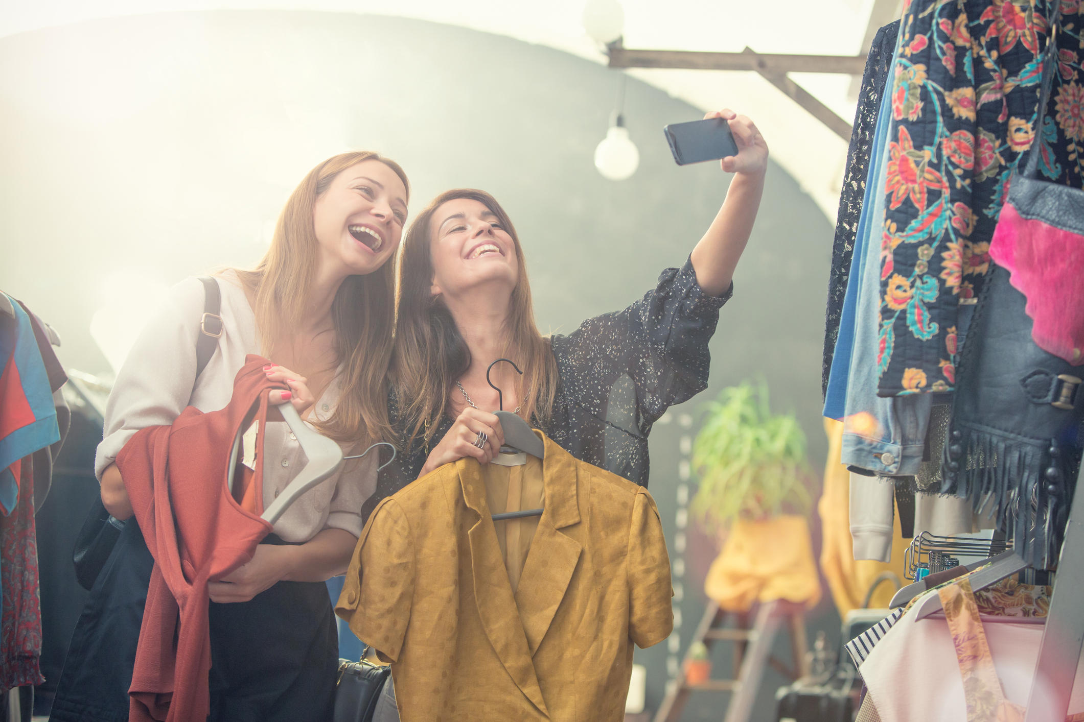 Young blonde and brown hair friends enjoy in secondhand clothing shop