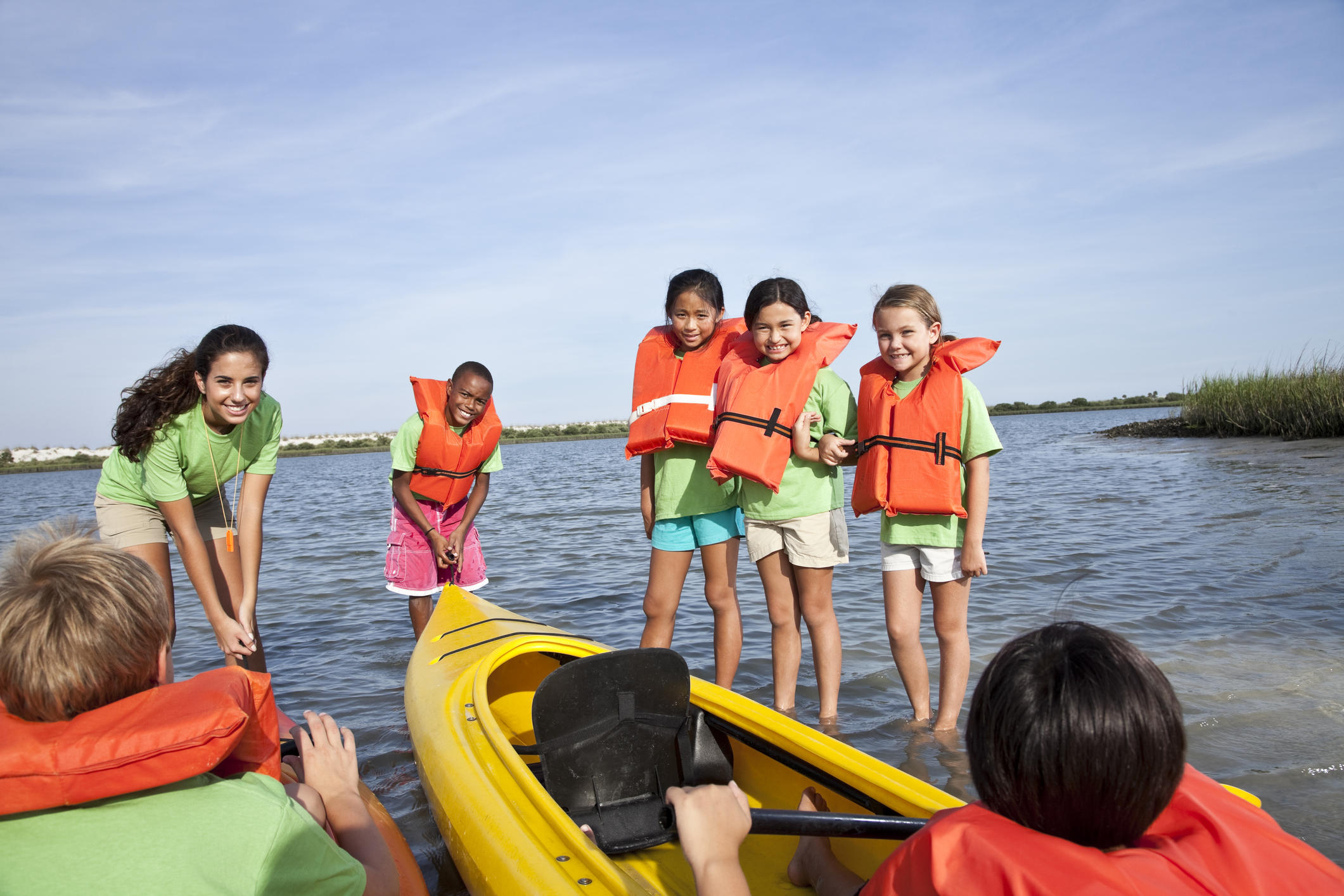 Teenage girl and group of children with kayaks at water sports camp.