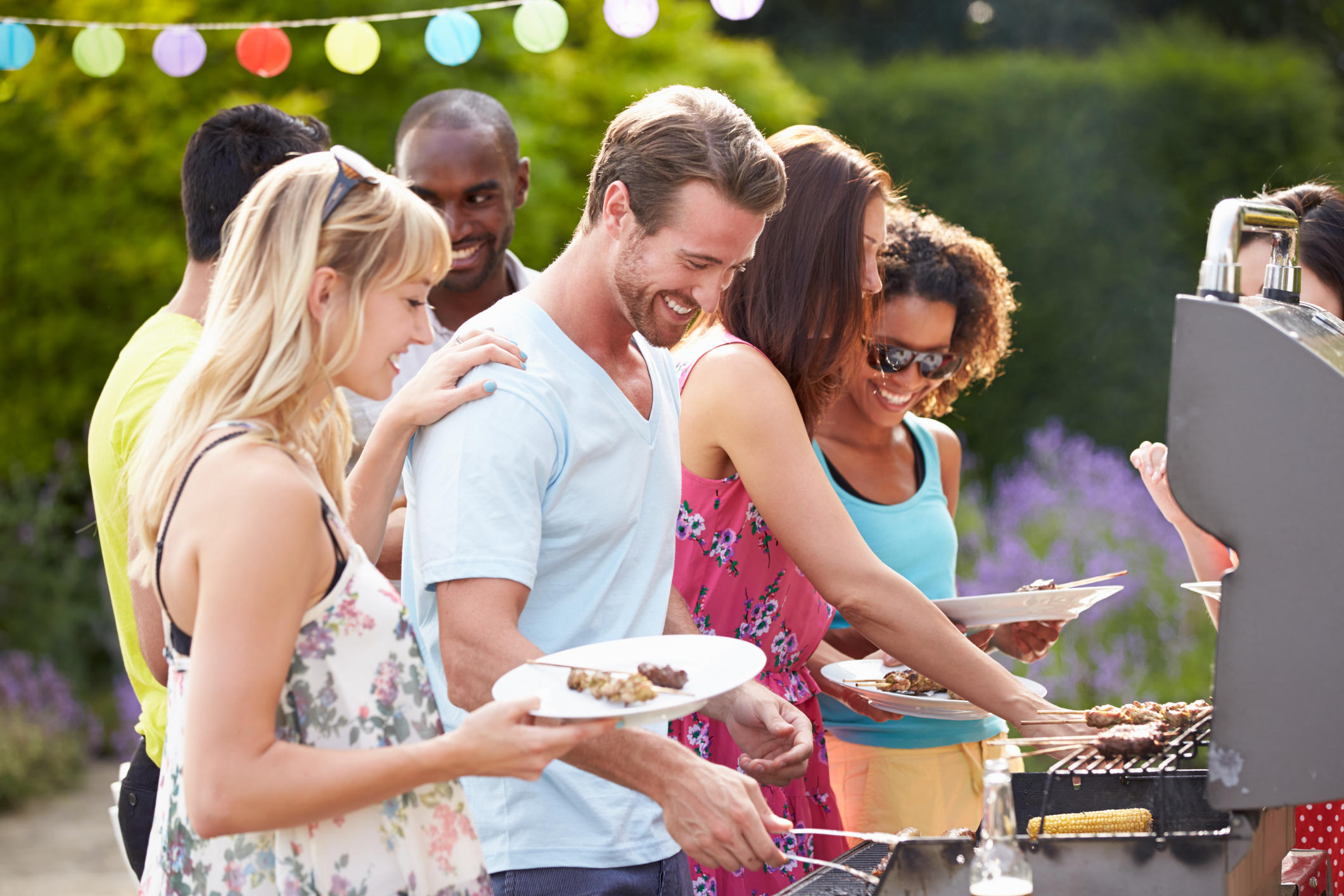 Group Of Friends Having Outdoor Barbeque At Home In Garden