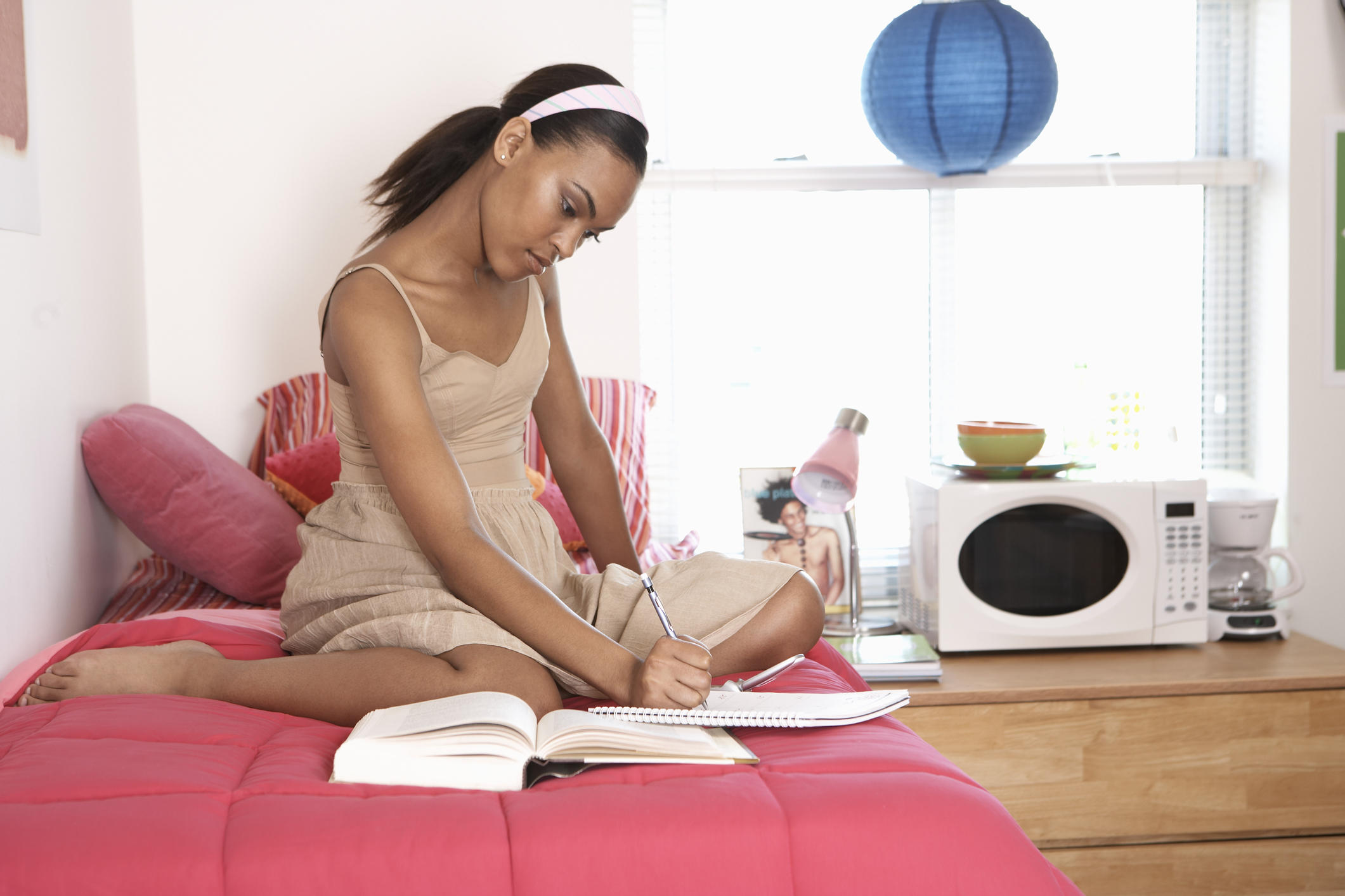 Young woman writing in notebook on bed in dorm room