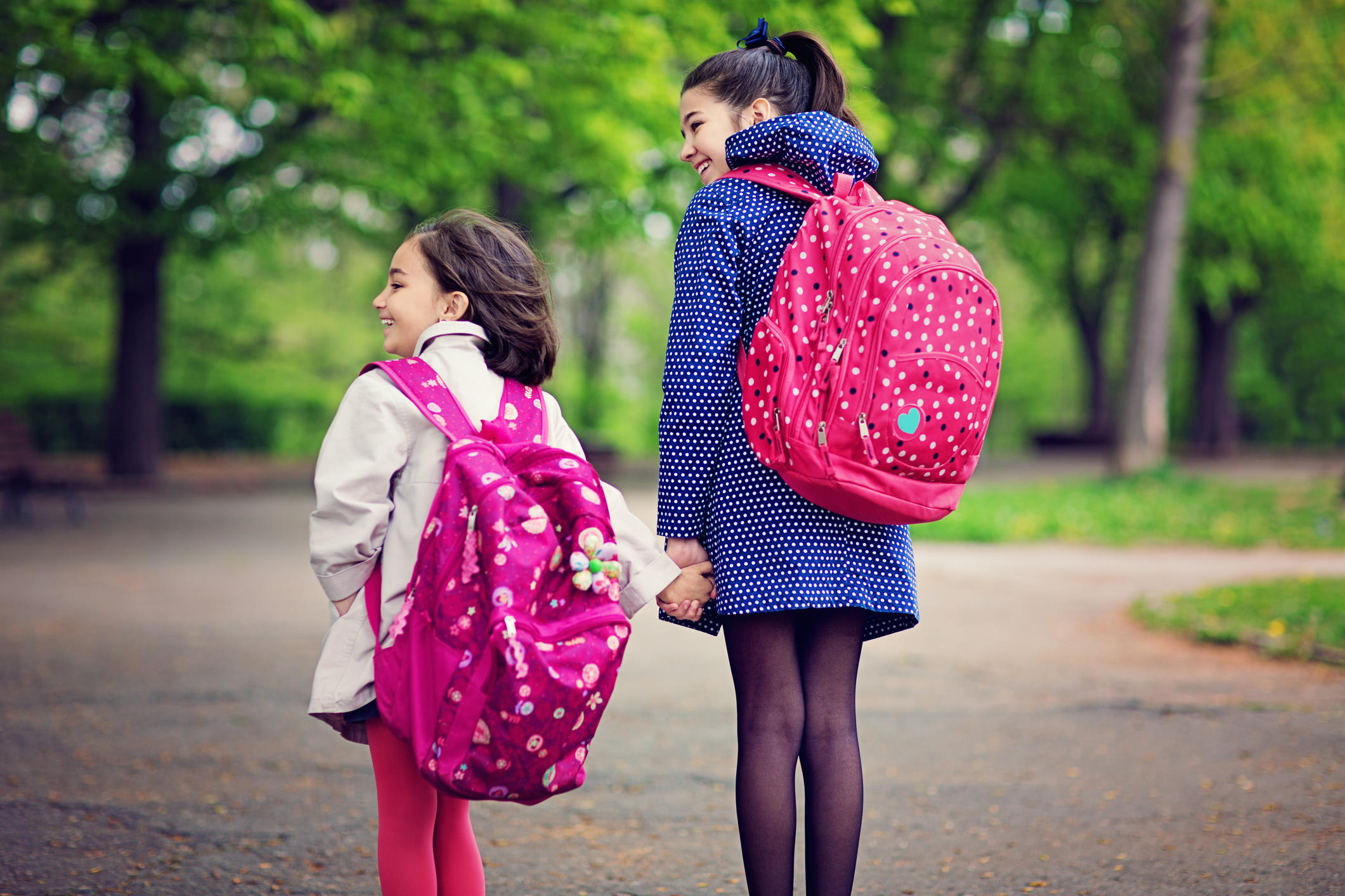Two sisters are going to the school pass throught the local park.