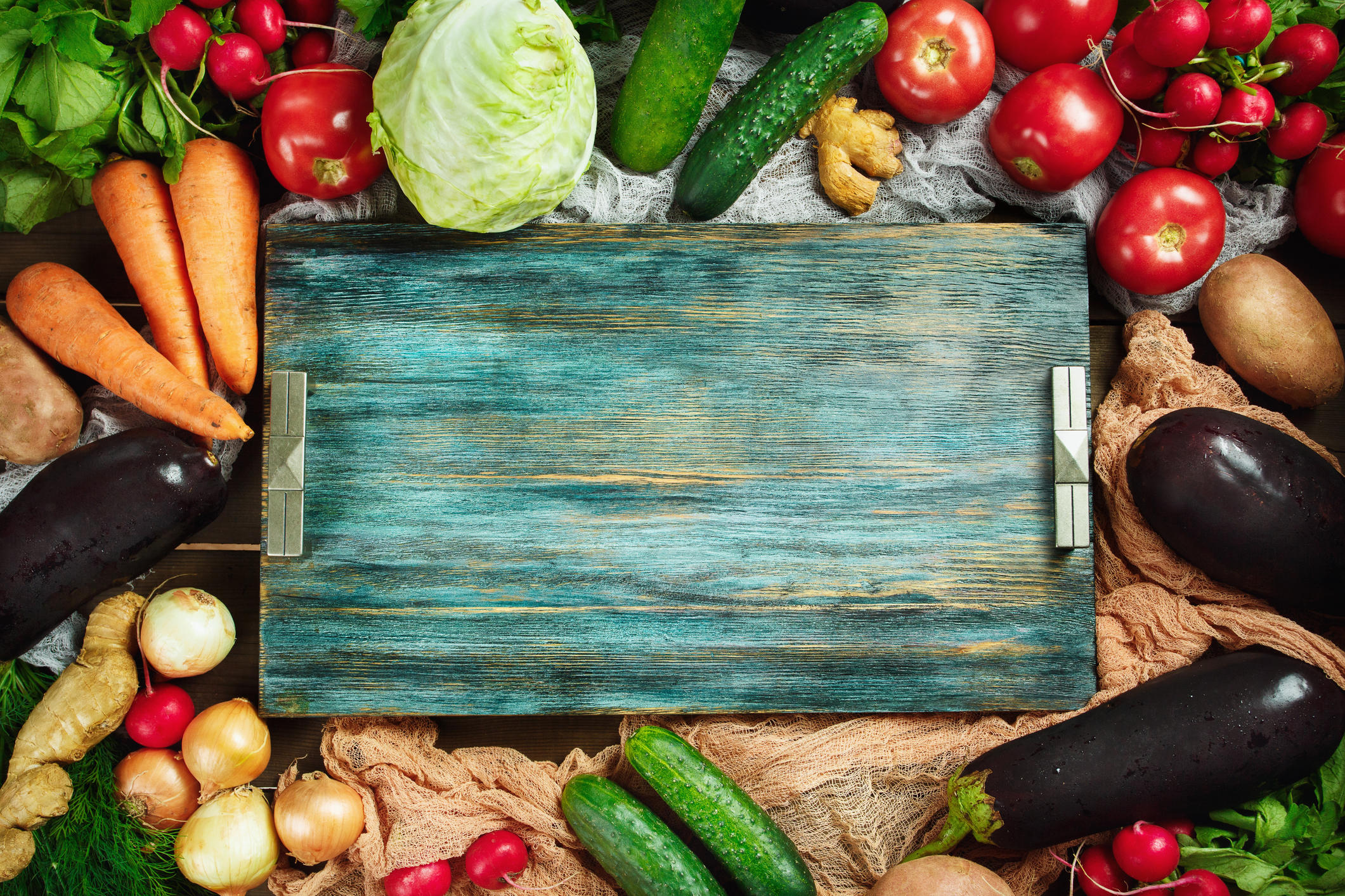 Border composition  made with fresh vegetables on wooden rustic table with blue vintage tray. Top view, space for text. Eggplants, cabbage, carrot, tomato, onion and other.
