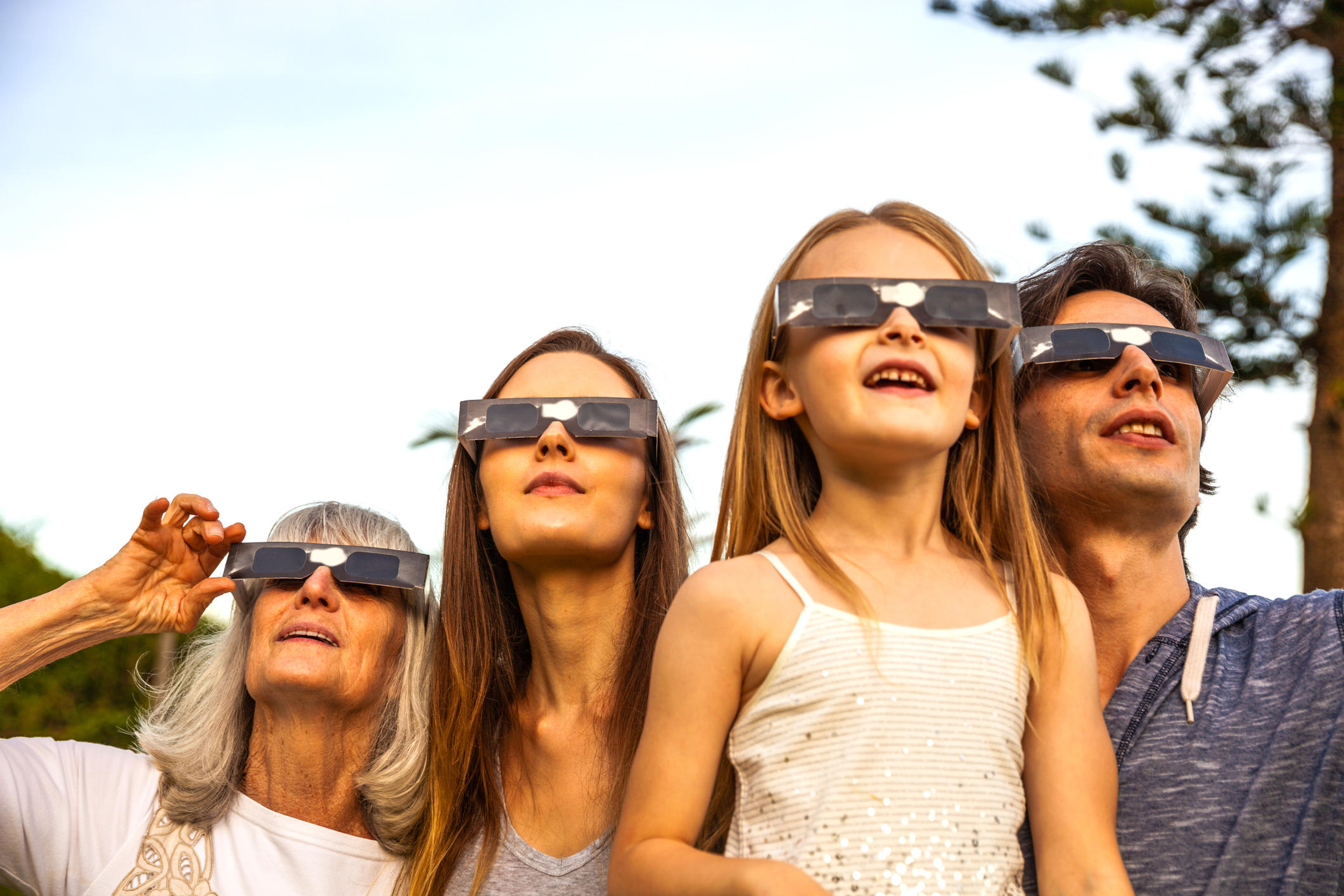 Family looking at Solar Eclipse using solar glasses.