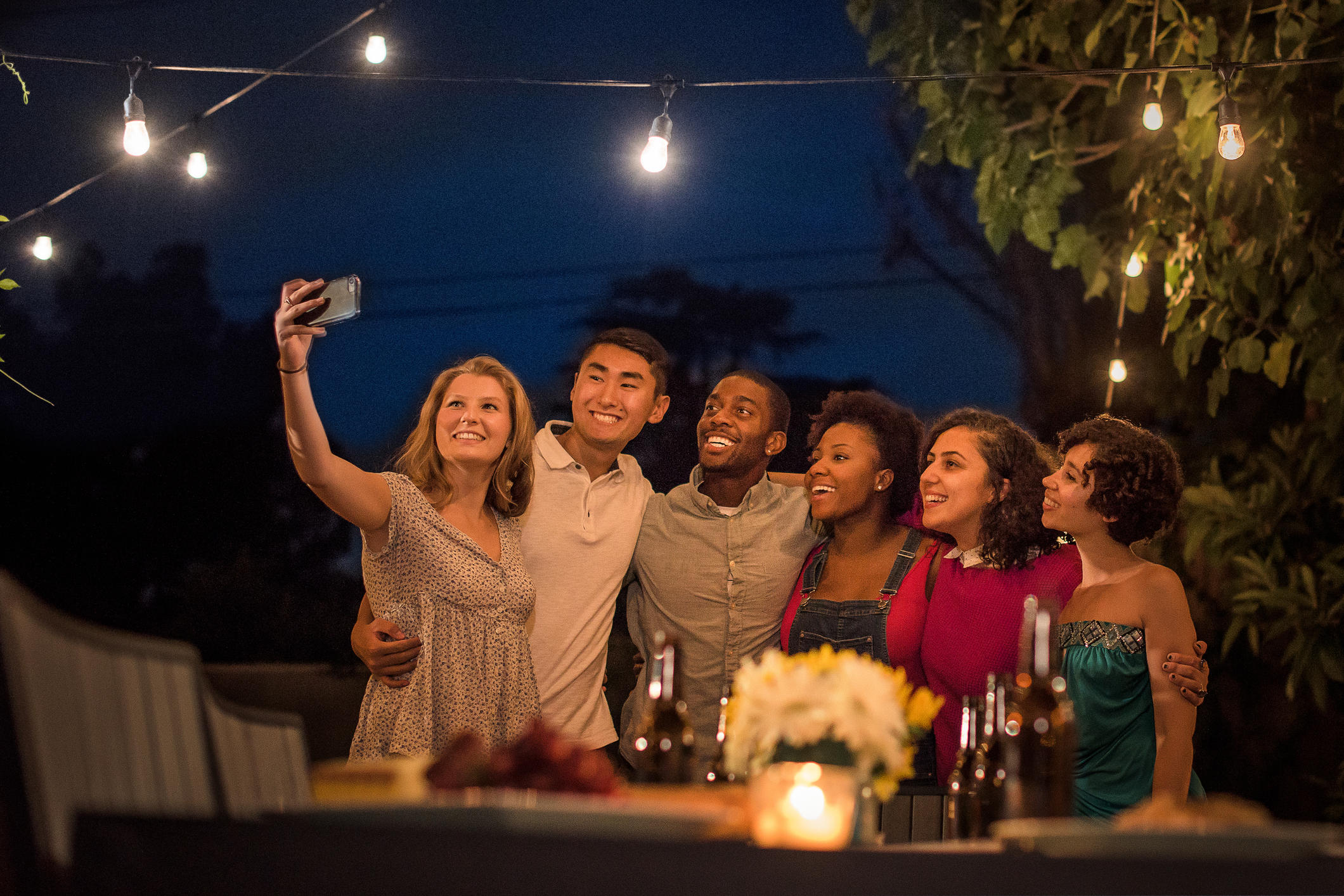 Multi ethnic hipsters all gathered around taking a group selfie at a summer BBQ.