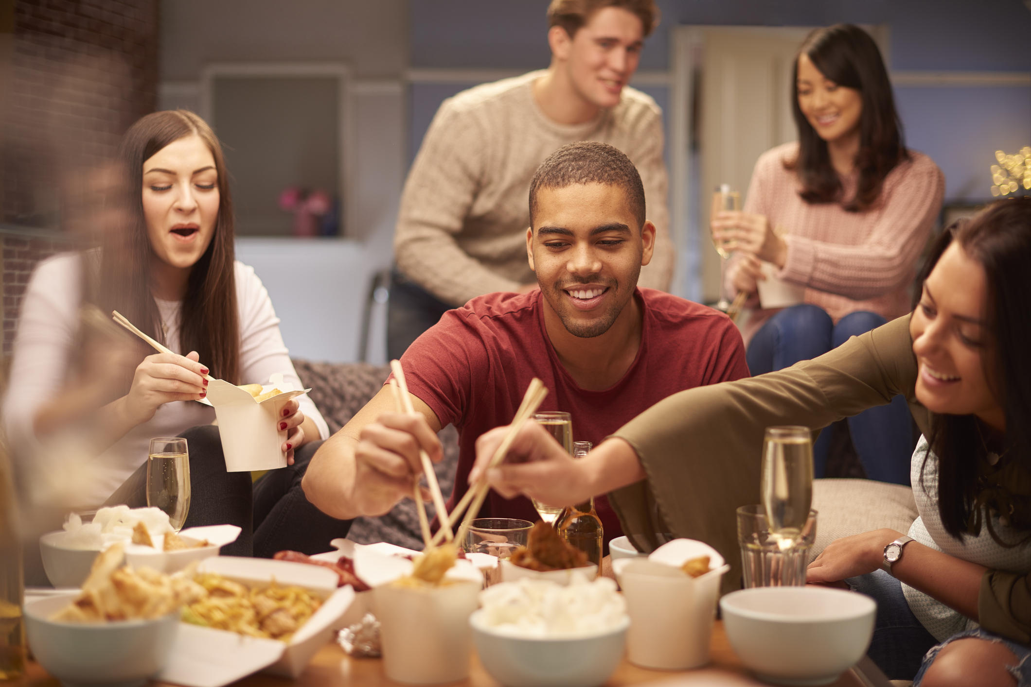 a group of young friends sit on the sofa and share a chinese take away meal , chatting and laughing with each other as they use their chopsticks to eat .
