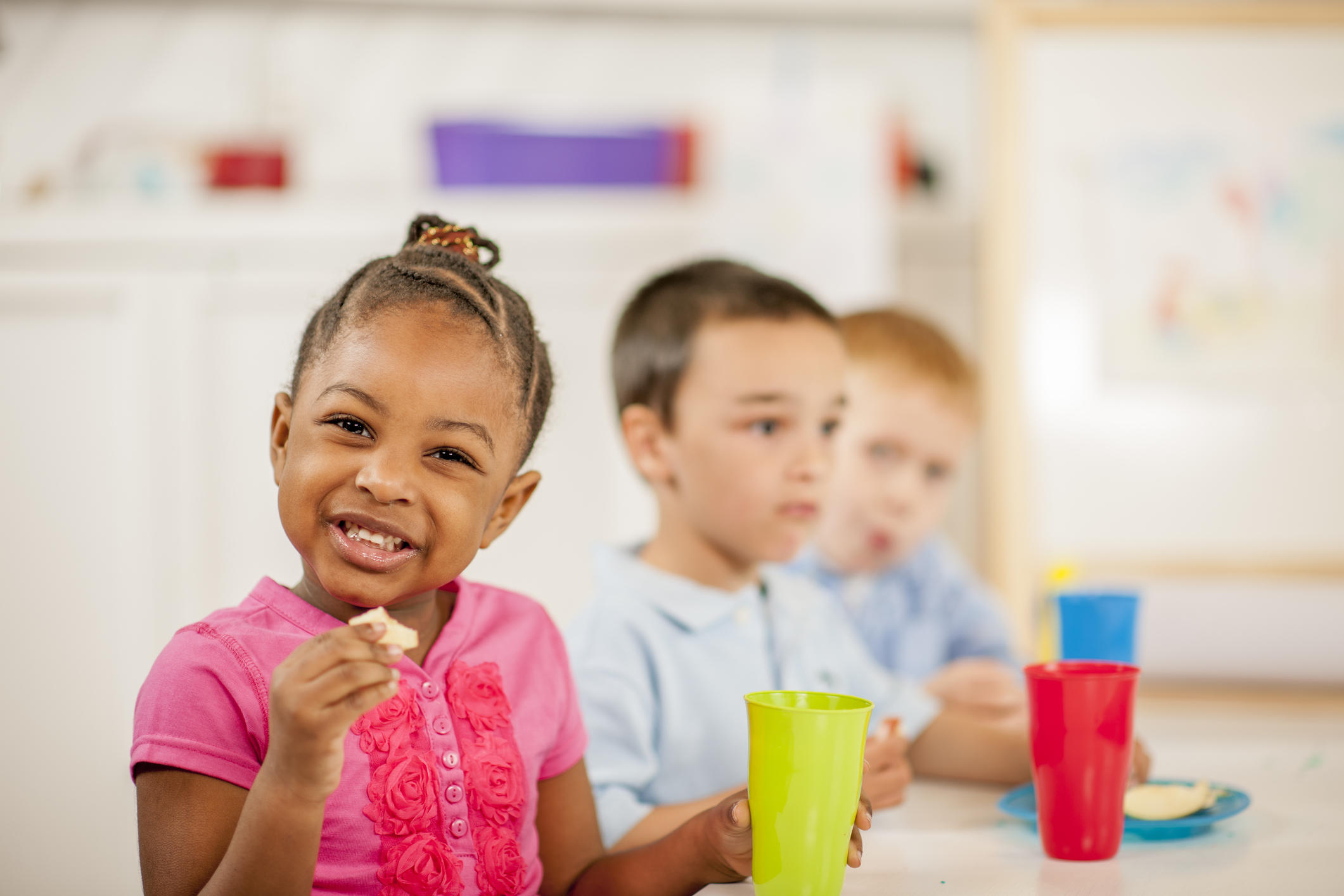 A  group of elementary age children are sitting at a table eating lunch together. One girl is smiling and looking at the camera.