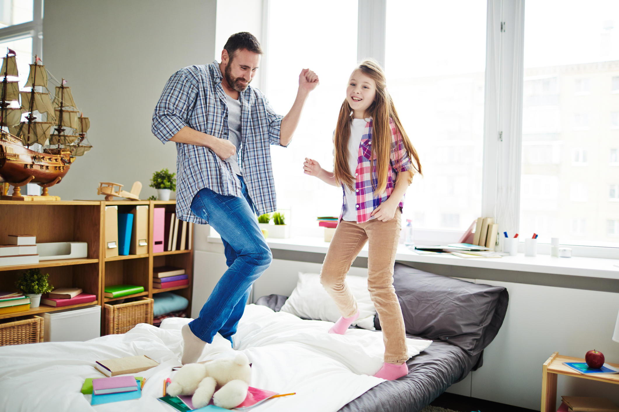 kids dancing on a bed