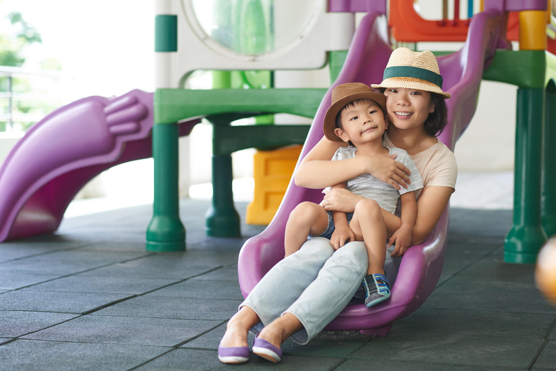 mom sliding down the slide with kid