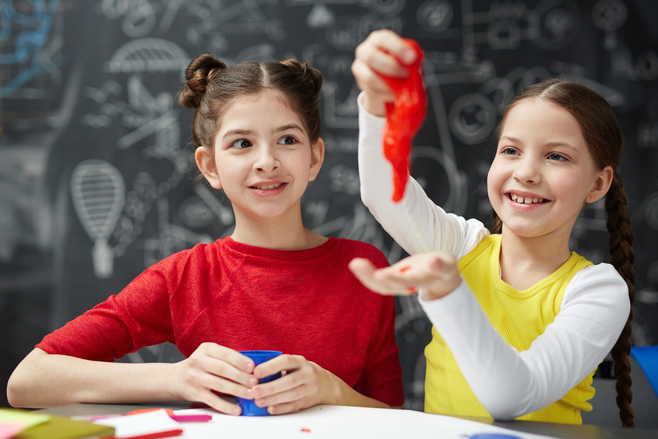 Playful girl having fun with red slime while her friend looking at this