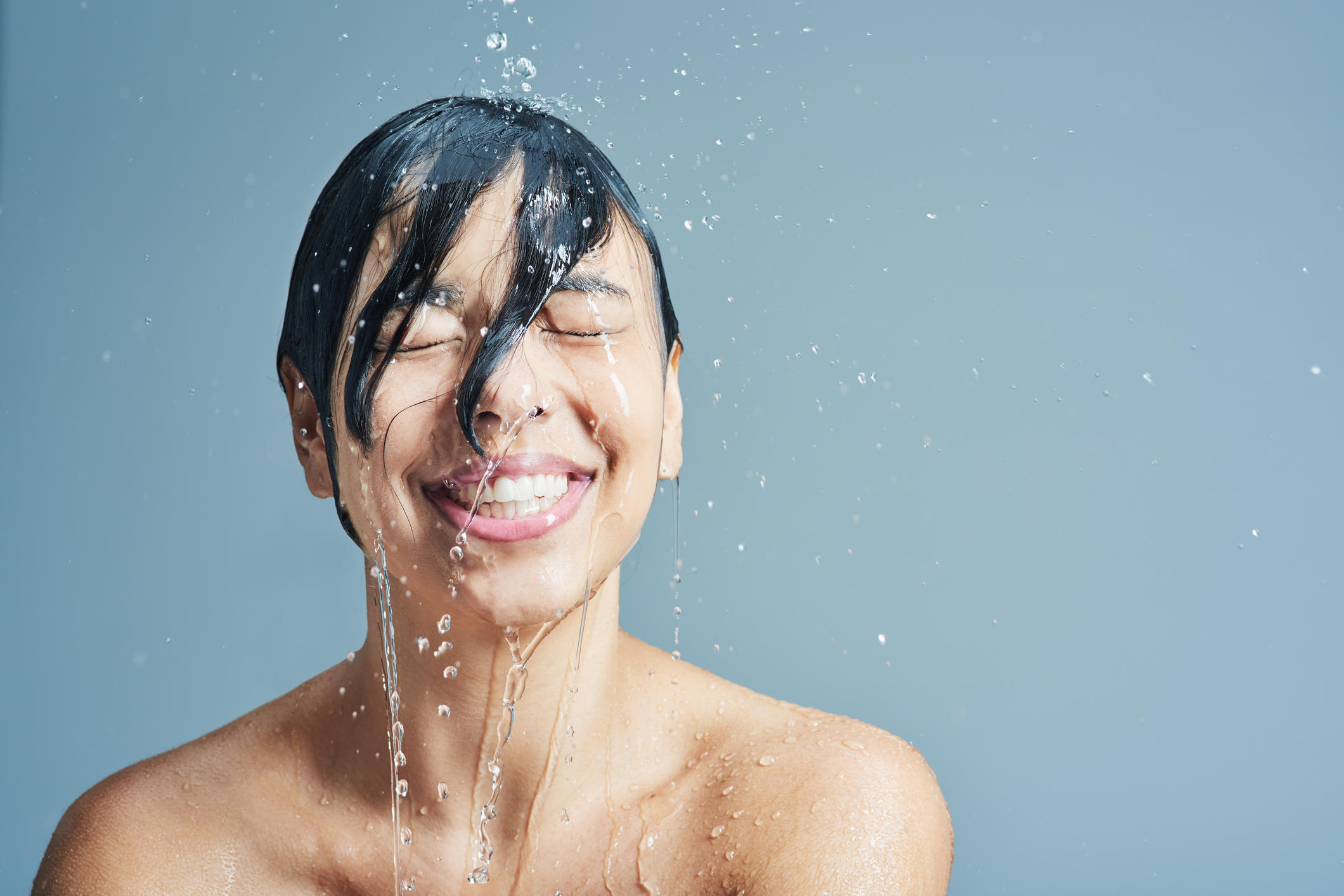 Shot of a young woman having a refreshing shower against a blue background