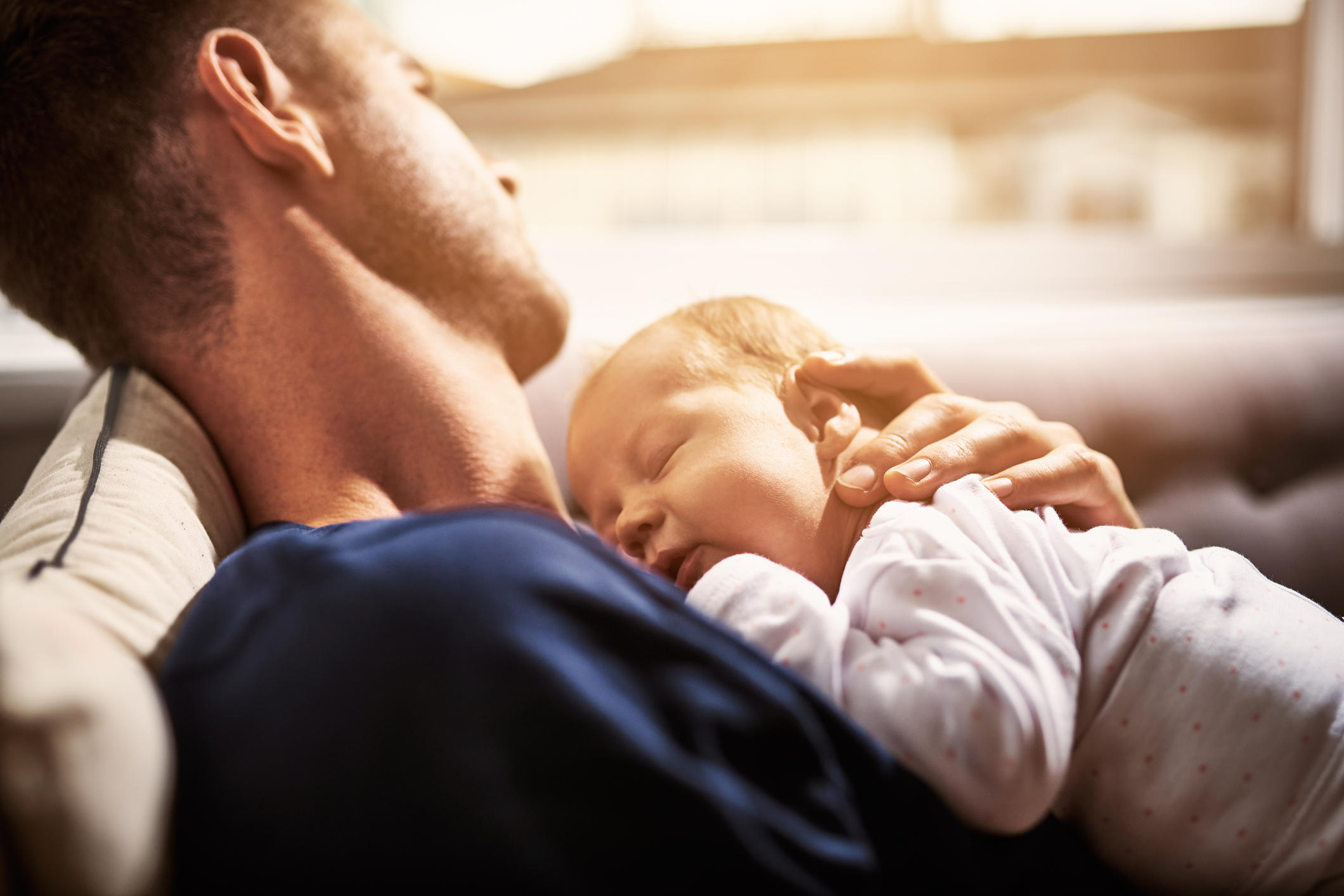 Shot of an adorable baby girl sleeping on her father's chest at home