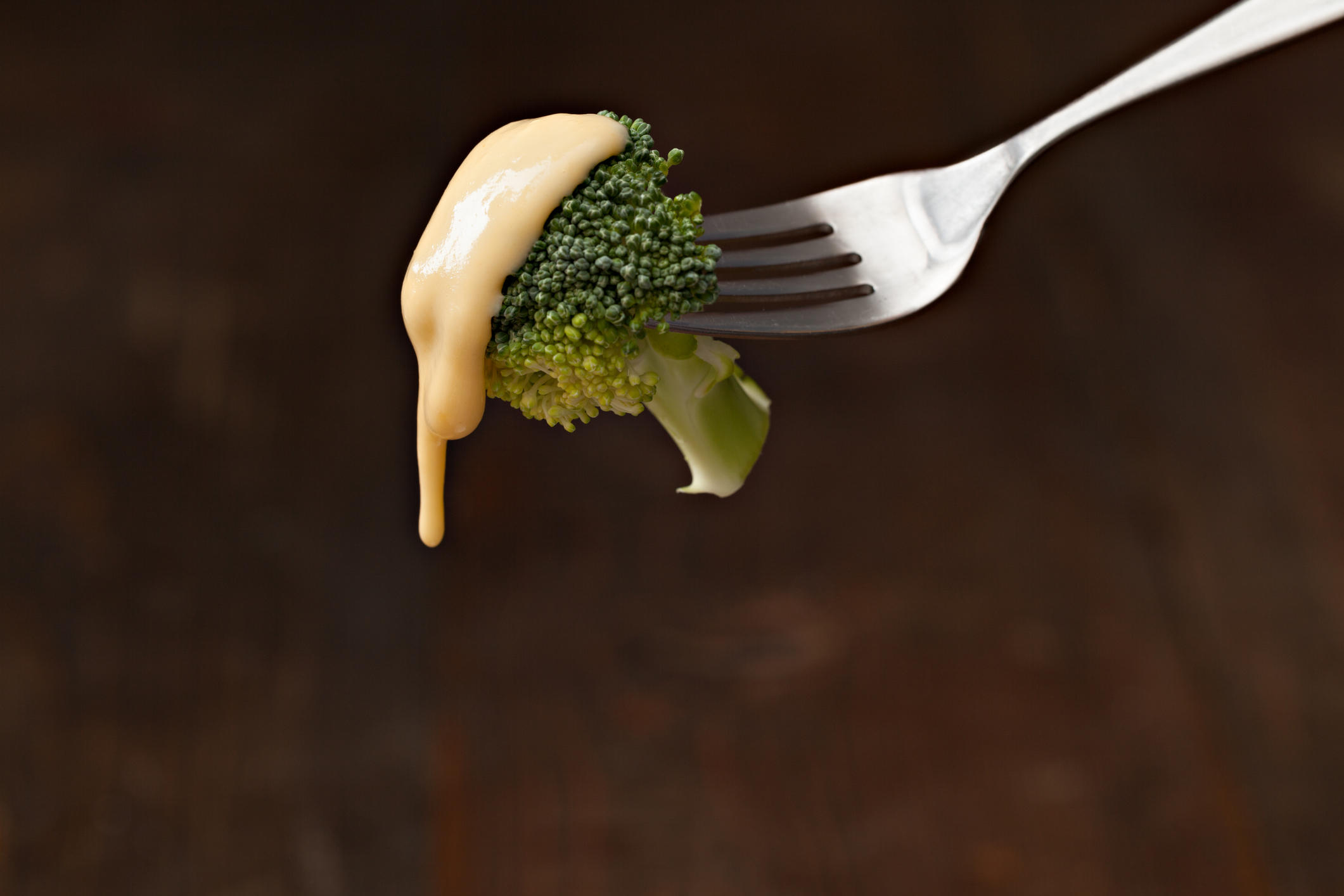 A close up horizontal photograph of a fork with a bite of broccoli topped with golden cheese sauce. Isolated on black with ample copy space.