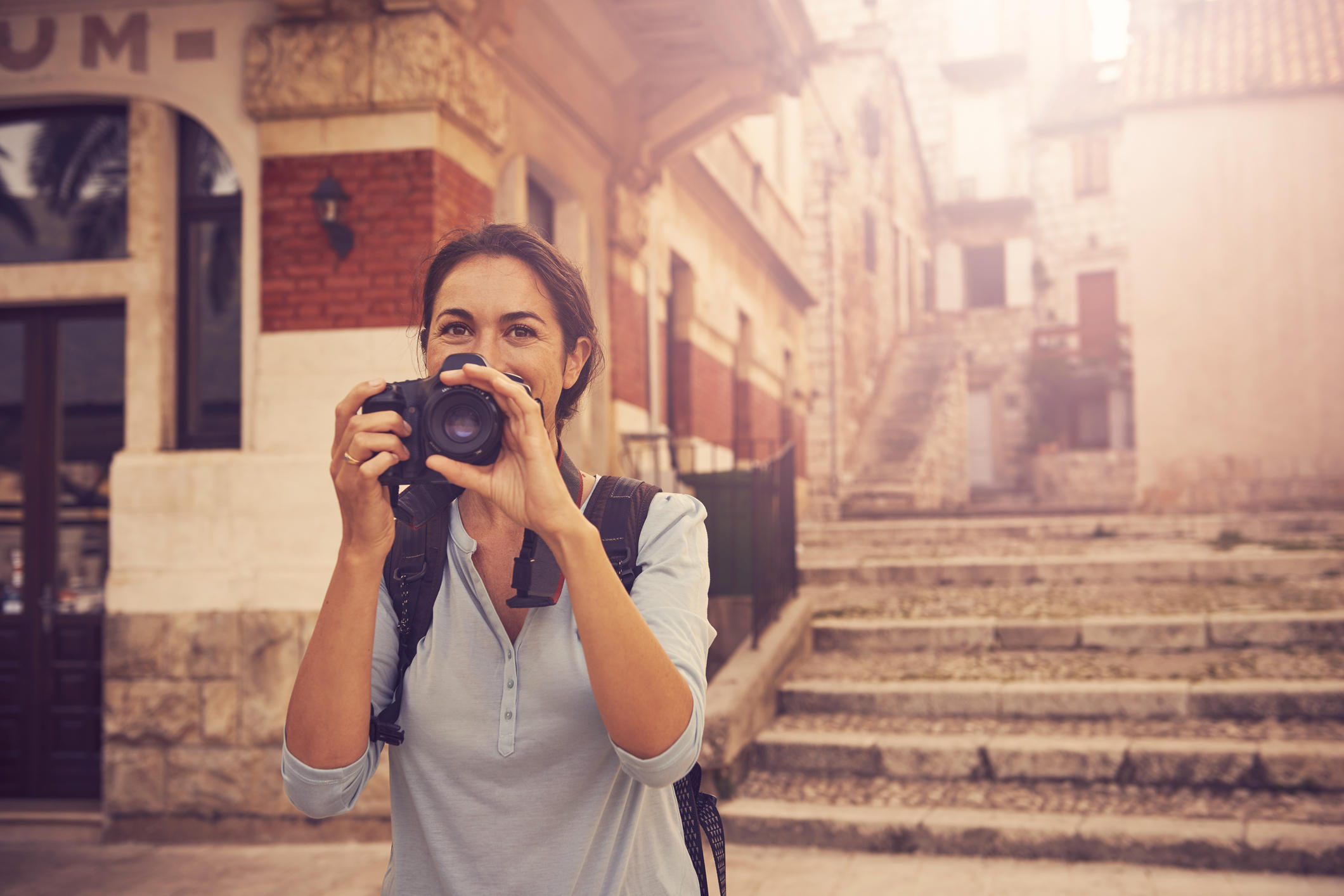 Shot of a woman taking photos while exploring a foreign city