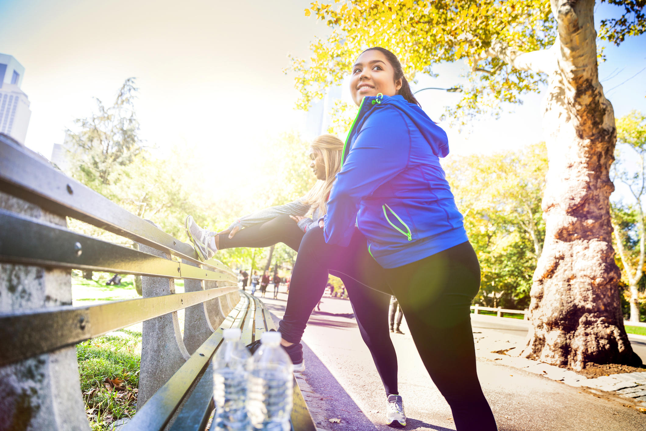 Two plus size women exercising in Central Park, New York during a beautiful day.