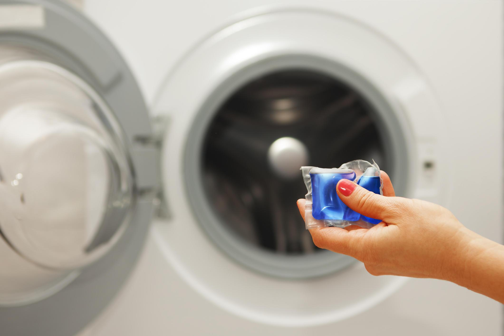 gel caps in hand for washing mashine, liquid coloured detergent