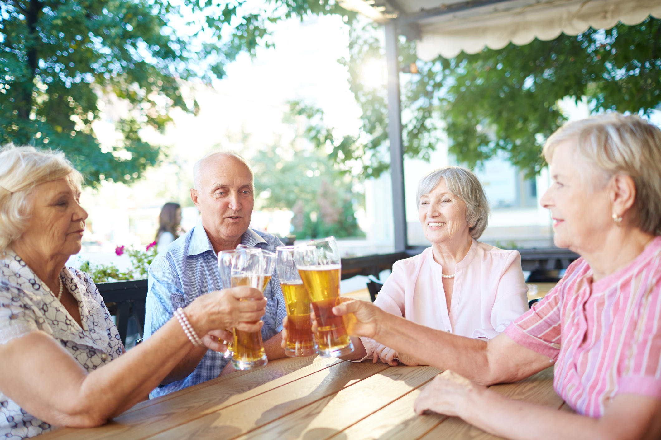 Group of elegant-looking elderly people sitting in outdoor pub and clanging glasses together with joy