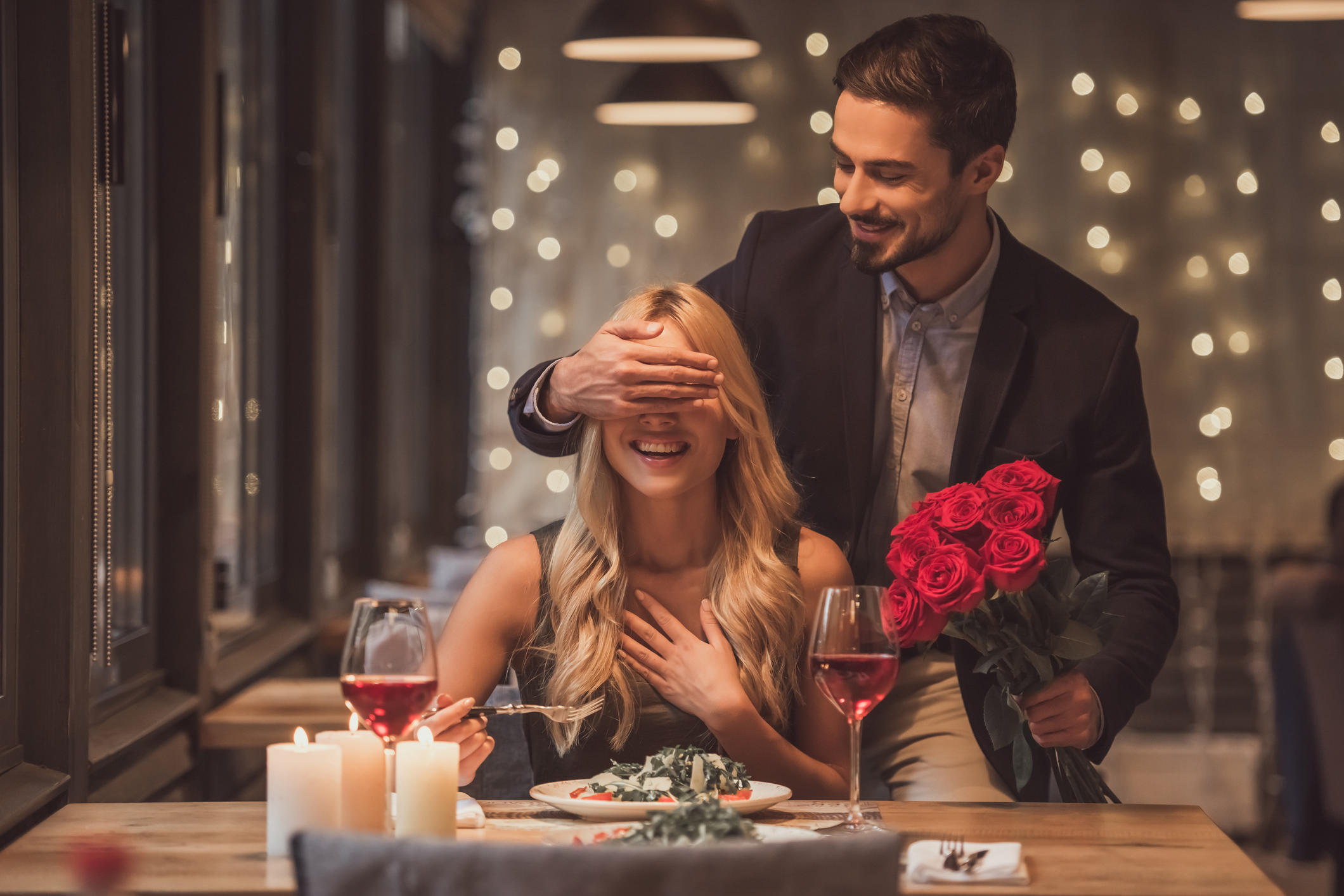 Handsome elegant man is holding roses and covering his girlfriend's eyes while making a surprise in restaurant, both are smiling