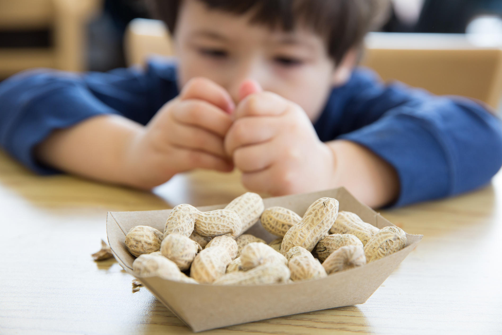 Little boy opening up peanuts to eat in a restaurant