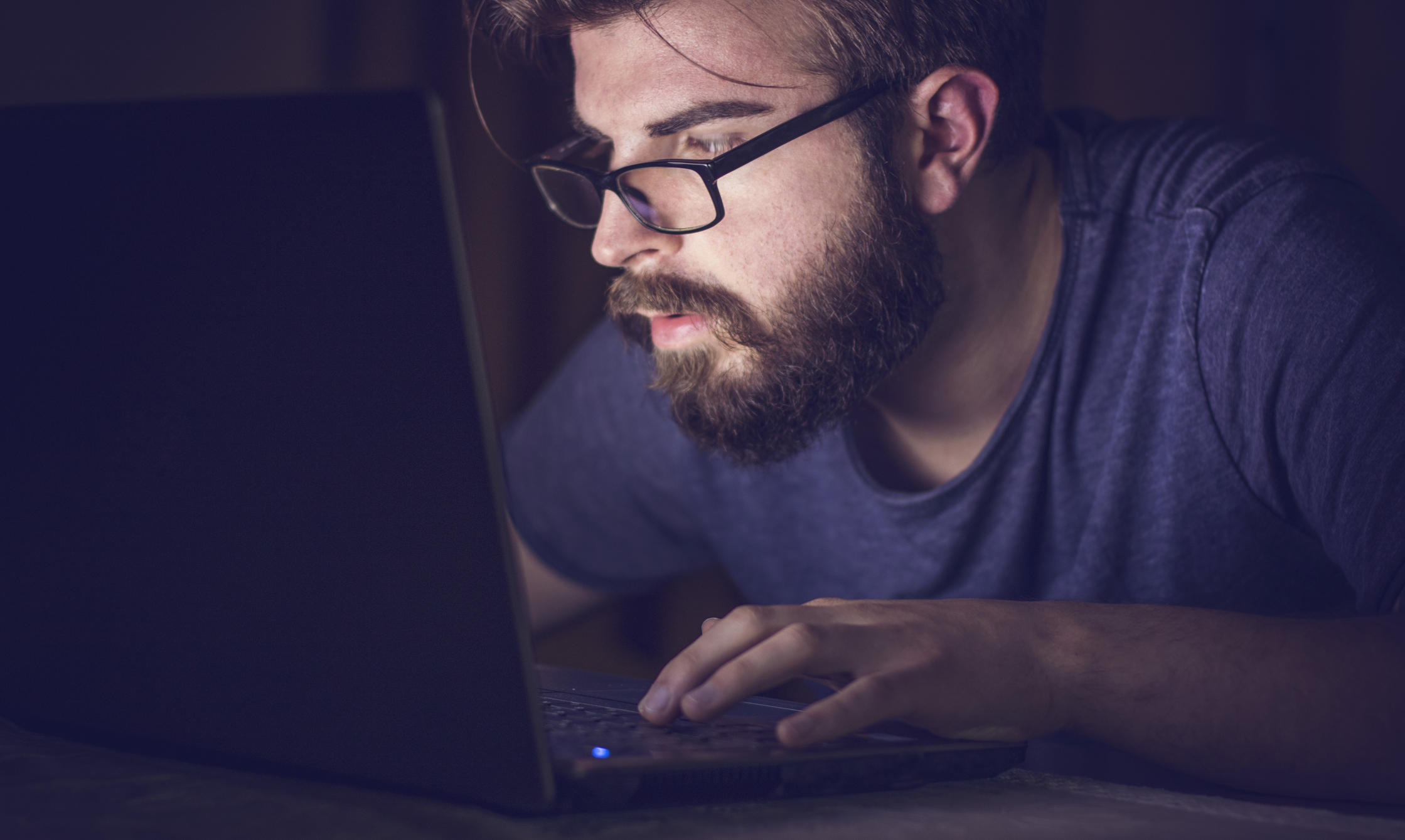 Bearded man working on his laptop late night