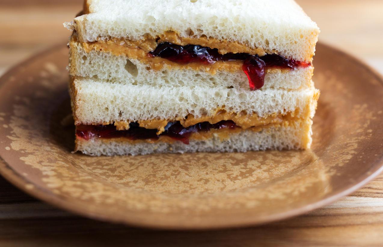 PB&J sandwich cut in half on a brown plate. Wooden background.