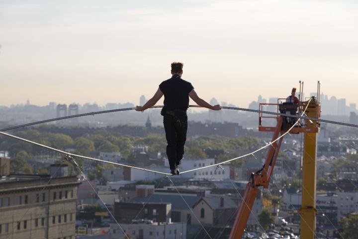 Nik Wallenda walks the high wire towards a crane.
