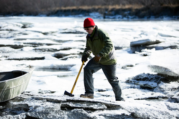 Atz Kilcher on the river's ice layer to check its thickness.
