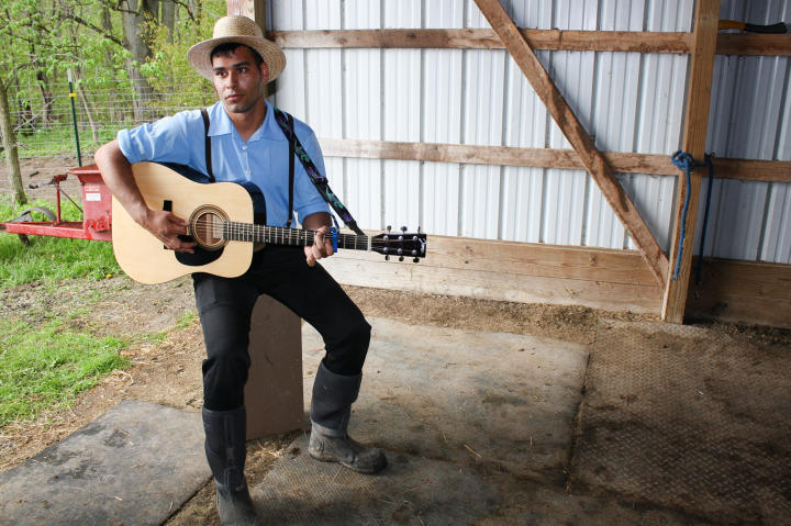 Playing the guitar (Johnny Cash-style) is a welcome respite after mucking the stalls.