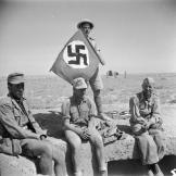 A British soldier in North Africa with his captured prizes of 3 German