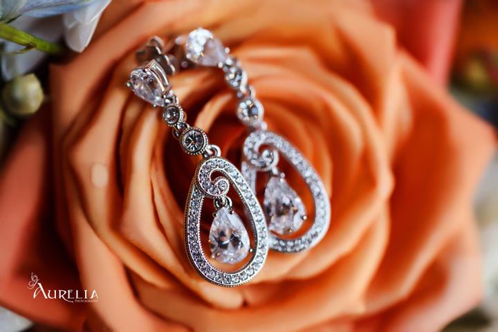 Karen's earrings lay on her orange bouquet.