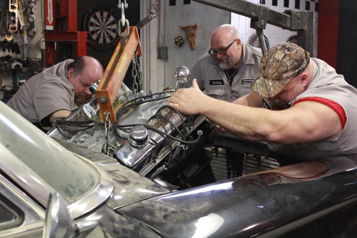 Chuck Kountz, Tommy Christmas, and Steve McGranahan installing a new hemi engine.