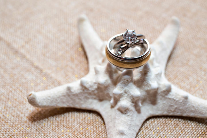 Bill and Jen's wedding bands and engagement ring sit on a star-shaped seashell.