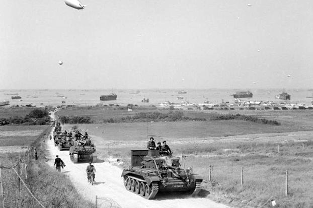 A Cromwell tank leads a column of armor inland from Gold Beach on Day 2 of the invasion..