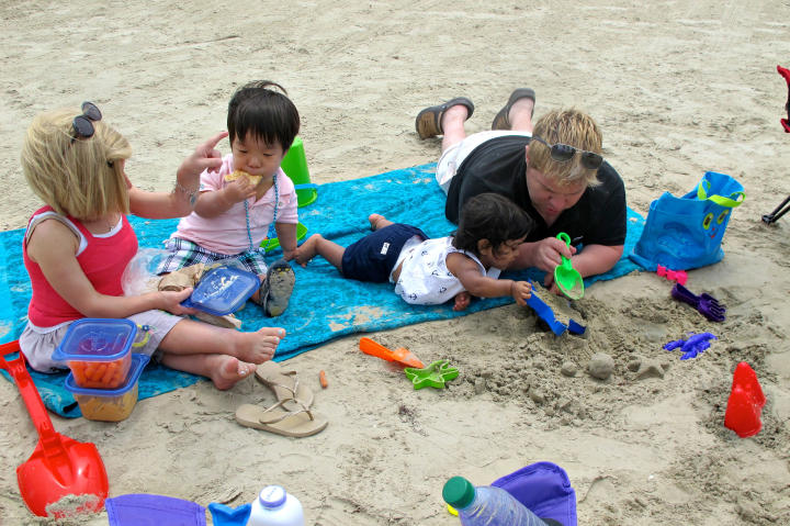 Lunchtime and playtime are combined at the beach.