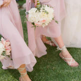 Bridesmaids in blush show off their bouquets and sandals.