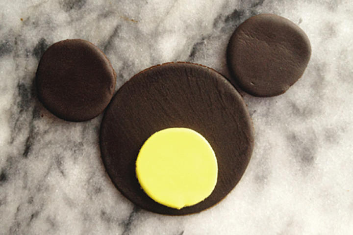 Add two brown fondant circles with diameters of approximately 1 1/2 inches equally spaced above the 3-inch-diameter circle of brown fondant.