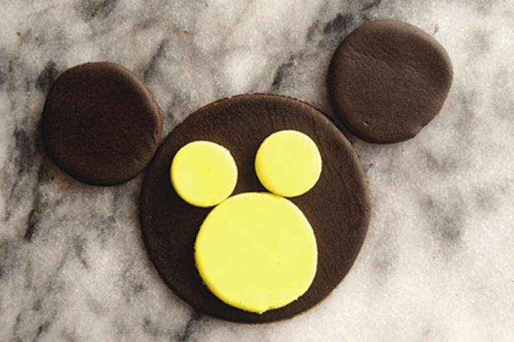 Using piping gel (or water), place the three yellow circles on the monkey face so that the larger circle is at the bottom of the cupcake and the two smaller yellow circles are equally spaced above the large yellow circle.