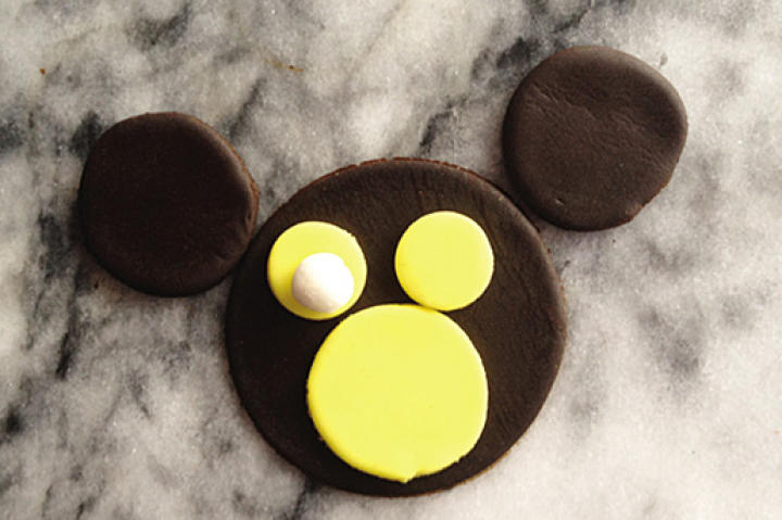 Also using piping gel to attach, place the white fondant balls on top of each of the smaller yellow circles to form the monkey's eyes.