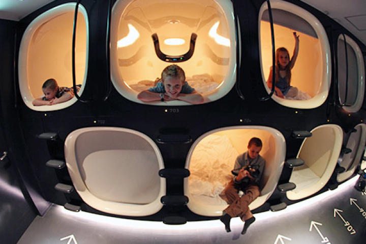 The kids enjoying their rooms in a Japanese capsule hotel.